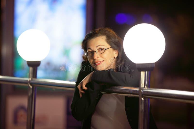 De volwassen vrouw in een zwart jasje stock afbeelding