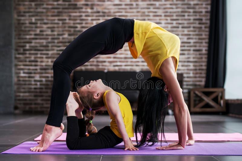 De volwassen vrouw en kindmeisje het praktizeren yoga samen thuis, volwassen status in brug stelt en jong geitje doend koningscob royalty-vrije stock afbeelding