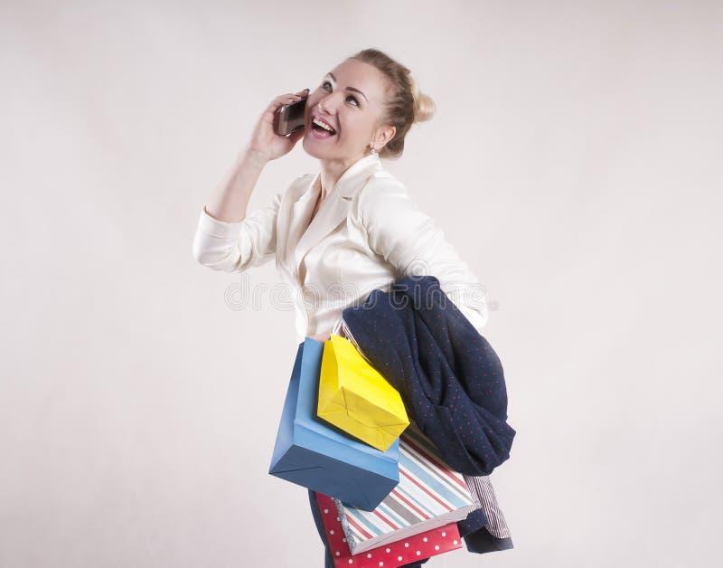 De volwassen vrouw met het winkelen doet levensstijl in zakken sprekend op de telefoonstudio voor winkelende studio modieuze pers stock afbeelding