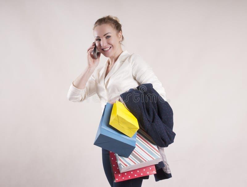 De volwassen vrouw met het winkelen doet het spreken op de telefoonstudio voor in zakken winkelende studio modieuze persoon royalty-vrije stock afbeeldingen