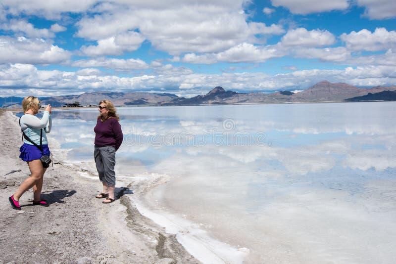 De volwassen vrouwelijke toerist neemt foto's van een andere toerist bij de Zoute Vlakten van Bonneville stock foto