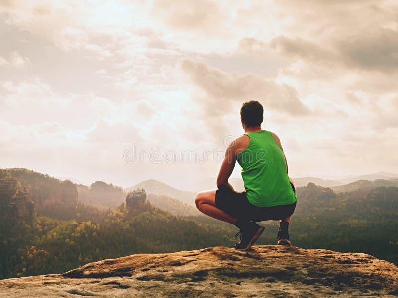 De volwassen wandelaar in zwarte borrels en het groene hemd zitten op bergrand Mens die van mening genieten royalty-vrije stock afbeelding