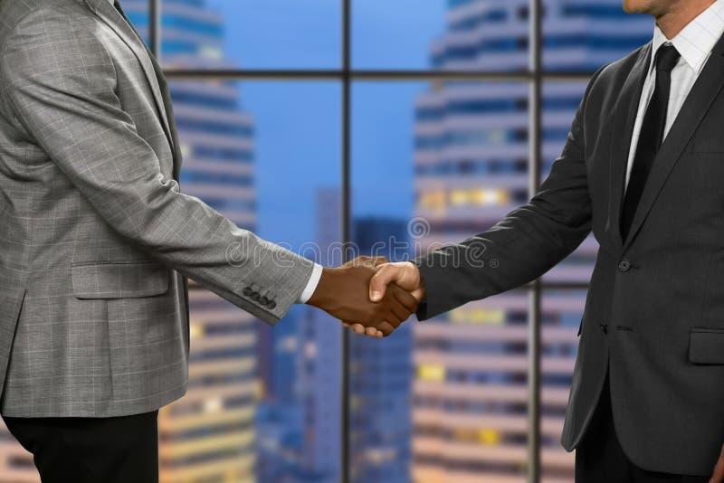 De volwassen zakenlieden schudden handen stock afbeelding