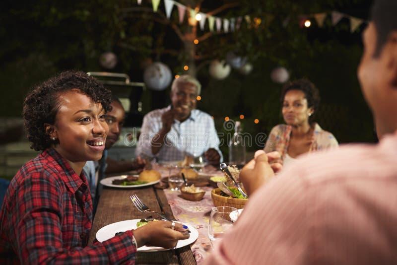 De volwassen zwarte familie eet diner in tuin, over schoudermening royalty-vrije stock foto