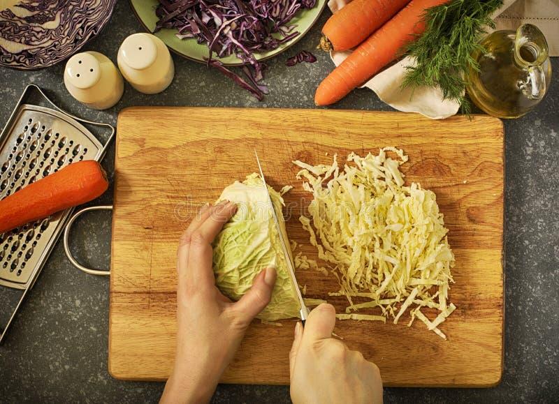 De voorbereiding van de Coleslowsalade De besnoeiingsgroenten van vrouwen` s handen voor salade royalty-vrije stock afbeelding