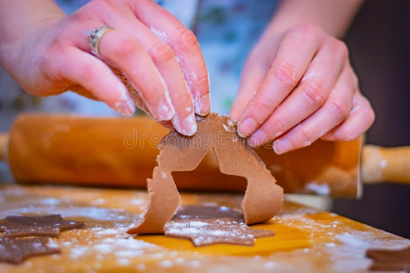 De voorbereidingen voor Kerstmis, de handen van een vrouw houden een stuk van cake voor de sterren van het peperkoekkoekje bijna  stock foto's