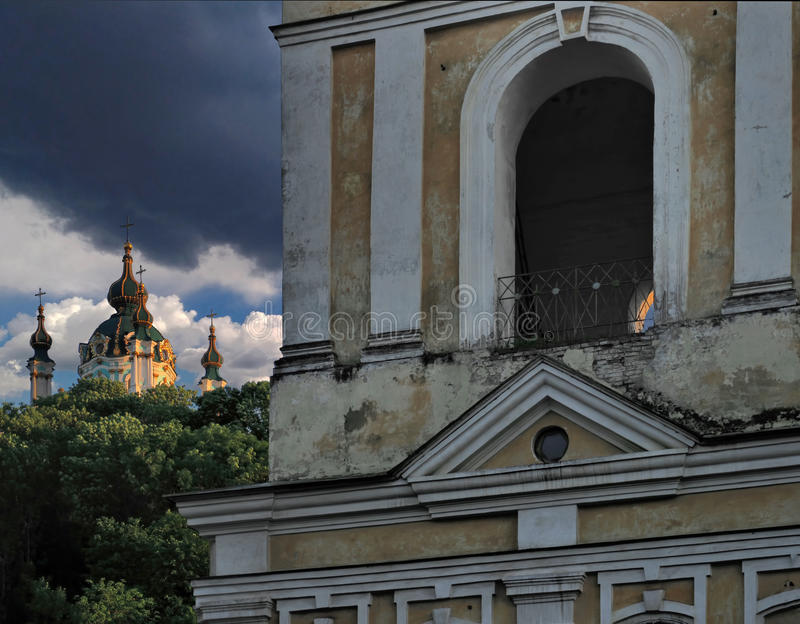 De voorgevel van de oude dilapidated Orthodoxe kerk op de achtergrond van de koepel van St Andrew ` s Kerk in Kiev royalty-vrije stock afbeeldingen