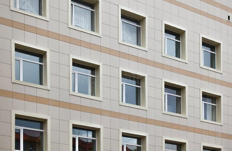 De voorgevel van een klinisch gebouw met meerdere verdiepingen De muren met vele vensters zijn gebeëindigd met plastiek stock afbeelding