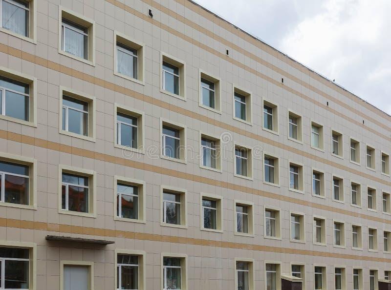 De voorgevel van een klinisch gebouw met meerdere verdiepingen De muren met vele vensters zijn gebeëindigd met plastiek royalty-vrije stock afbeelding