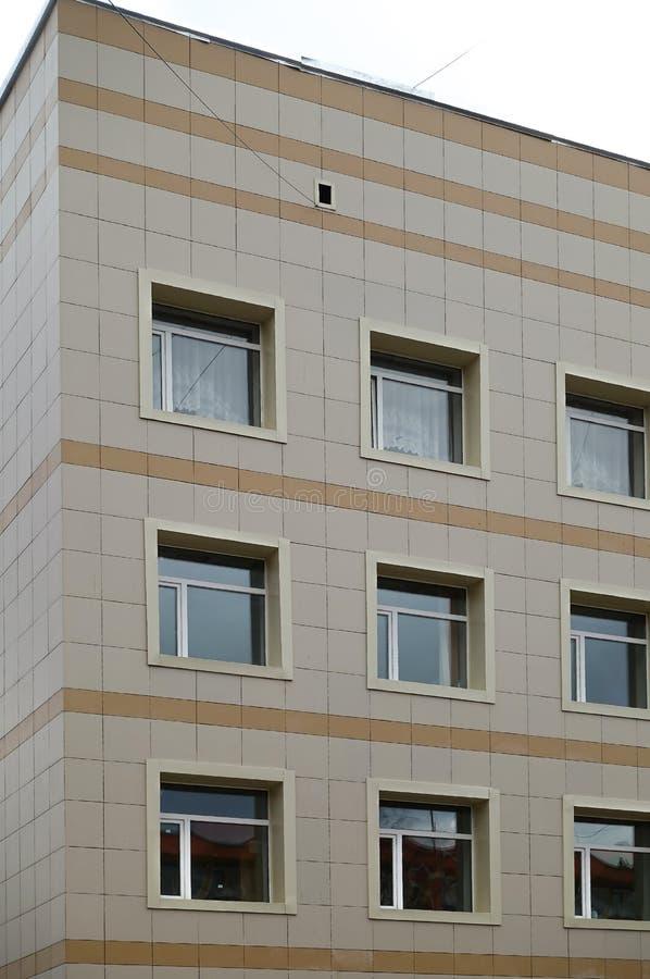 De voorgevel van een klinisch gebouw met meerdere verdiepingen De muren met vele vensters zijn gebeëindigd met plastiek stock foto's