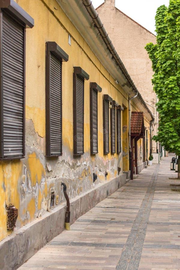 De voorgevel van een oud huis met vlokkige gele muren stock foto