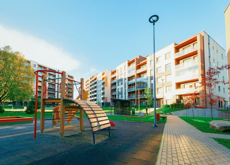 De voorgevelarchitectuur van het flat woonhuis met de zonlicht van de kindspeelplaats stock fotografie
