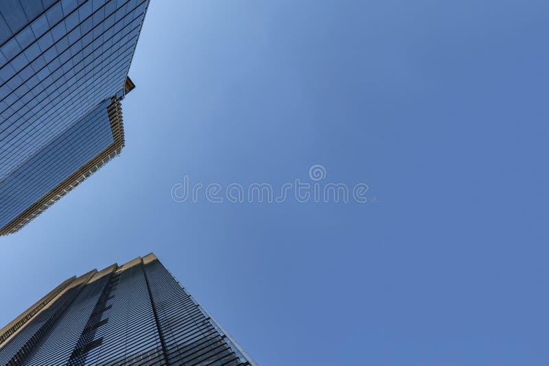 De voorgevels van het wolkenkrabberglas bij een heldere zonnige dag op de blauwe hemelachtergrond Economiefinanciën en zakelijke  royalty-vrije stock afbeelding