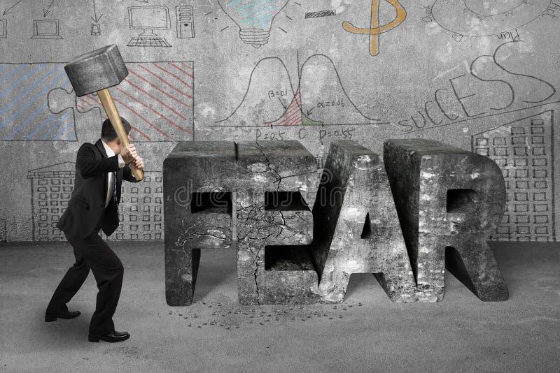 De voorhamer die van de zakenmanholding vrees concreet woord raken met stock afbeeldingen