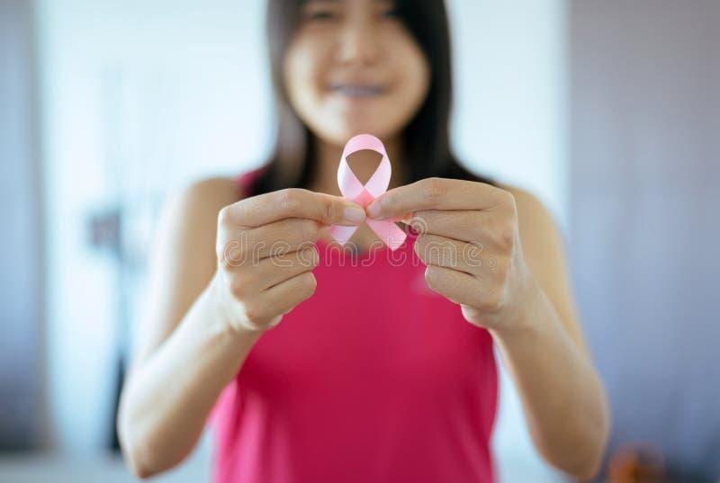 De voorlichtingsconcept van borstkanker, Aziatische vrouwenhanden die roze lint houden stock fotografie