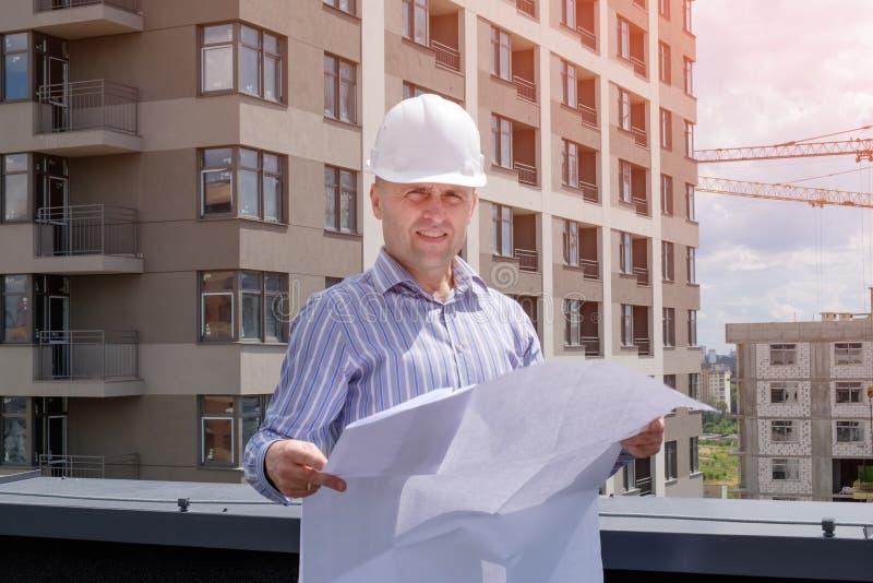 De voorman of de inspecteur in witte helm bekijkt het project royalty-vrije stock foto