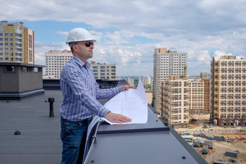 De voorman of de ontwikkelaar in witte helm en de zonnebril op dak bekijken het project op de bouwwerf stock foto's