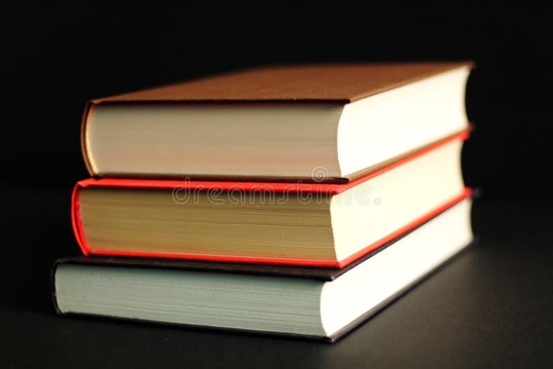 De voorraad van boeken in harde dekking, zwarte achtergrond, sluit omhoog stock fotografie