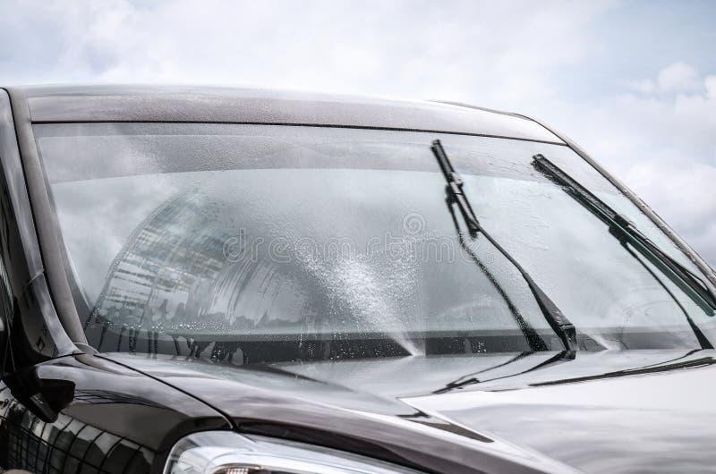 De voorruit van de wasauto met wissers en vloeistof stock afbeeldingen