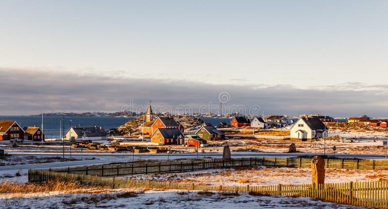 De voorstadpanorama van de Nuukstad met Inuit-huizen met overzees en de fjordachtergrond, Groenland stock afbeelding