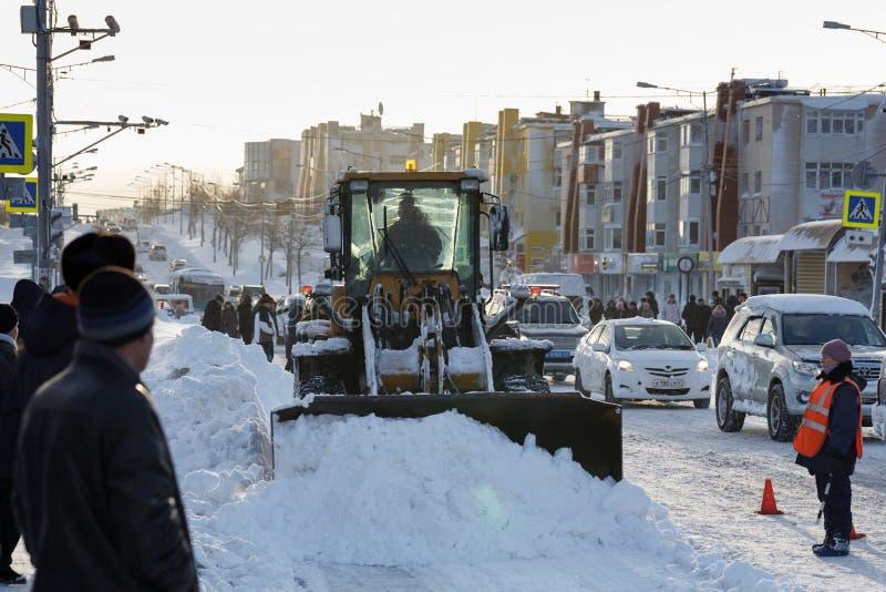 De voorwiellader maakt hoofdweg in stad na de wintersneeuwstorm schoon stock foto