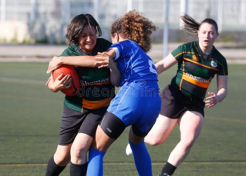 De voorzijde op hoogte en greep hogere lichaamsuitrusting tijdens rugbyvrouwen past playgame aan stock foto's