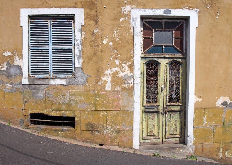De voorzijde van een oud verlaten geel huis met blauw shuttered vensters en sloot groene houten deur met afschilferende schilverf stock foto's