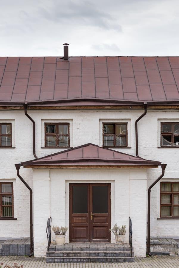 De voorzijde van het oude huis Hoofdingang, witte muren stock foto