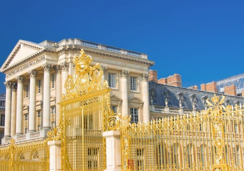 De voorzijde van het Paleis van Versailles en gouden omheining stock foto's