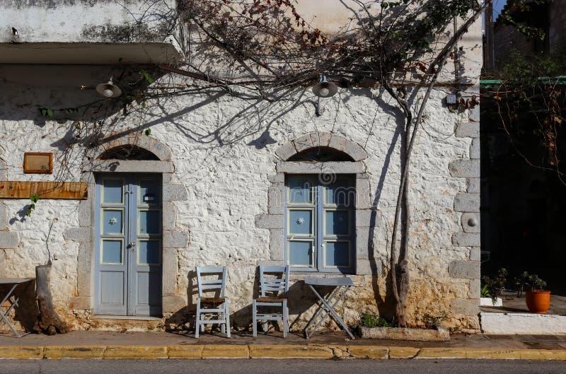 De voorzijde van kleine schilderachtige opslag of resturant met lijst en de stoelen op stoep sloten voor vakantie op hoofdstraat  stock foto