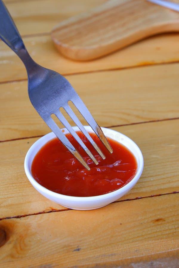 De vork dompelt in tomatensaus op houten lijst onder stock foto