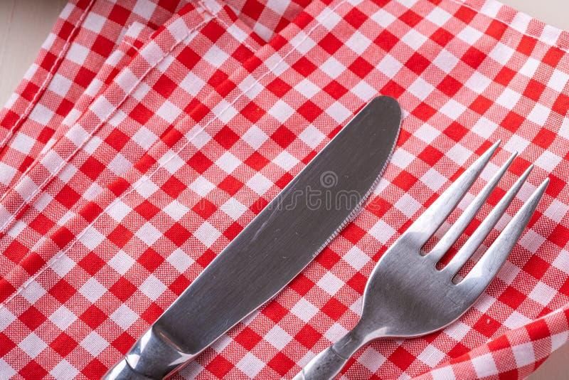 De vork en het mes van de besteklijst op rood tafelkleed, hoogste vlakke mening, leggen royalty-vrije stock afbeeldingen