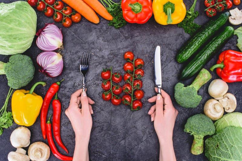 De vork en het mes van de persoonsholding boven gezonde verse groenten op zwarte royalty-vrije stock foto
