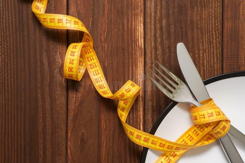 De vork en het mes zijn verpakt in gele metende band op de plaat Exemplaarruimte voor tekst Dieetreceptenschotels voor lunch Hoog royalty-vrije stock afbeeldingen