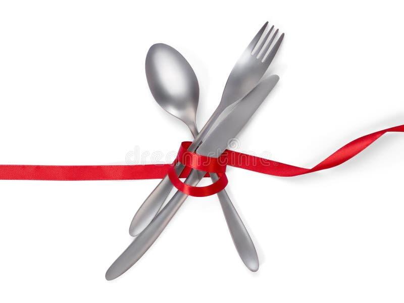 De vork, de lepel en het mes bonden met een rood die lint op wit w wordt geïsoleerd stock fotografie