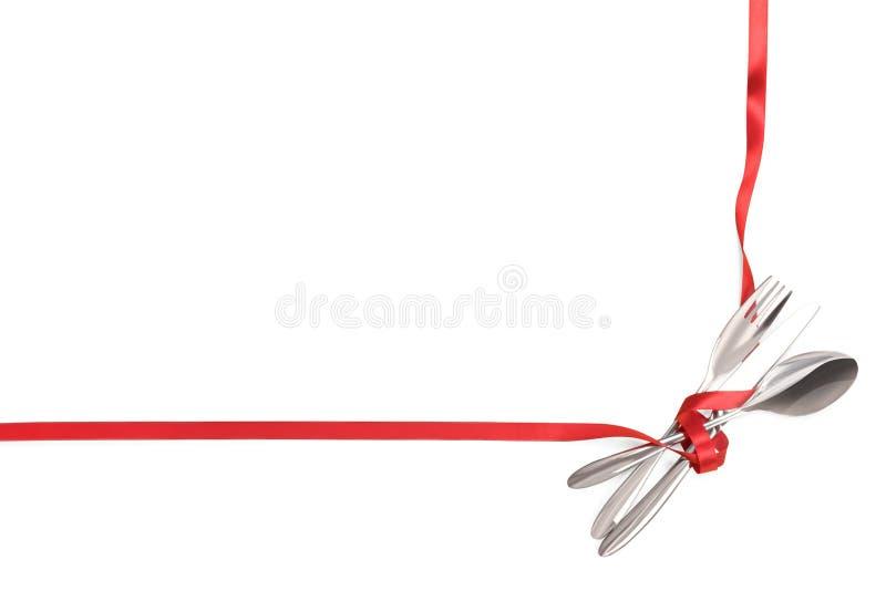 De vork, de lepel en het mes bonden met een rood lint dat met exemplaarruimte wordt geïsoleerd royalty-vrije stock afbeeldingen