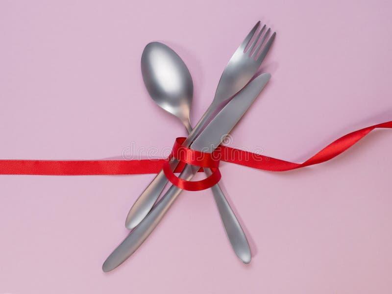 De vork, de lepel en het mes bonden met een rood lint op roze achtergrond stock afbeelding