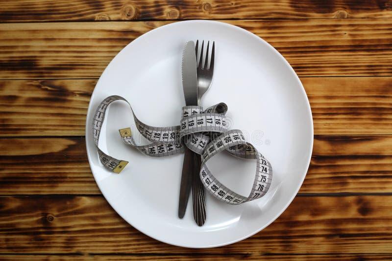 De vork met een verpakt mes, bandcentimeter ligt op een witte ronde ceramische plaat stock fotografie