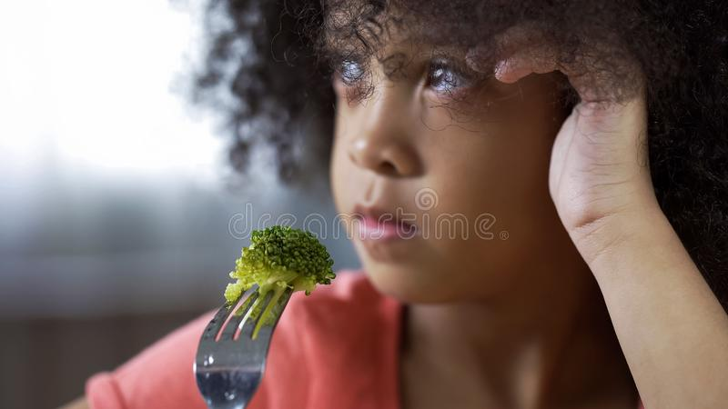 De vork van de het meisjeholding van Nice met stuk van broccoli, onsmakelijk voedsel stock afbeeldingen