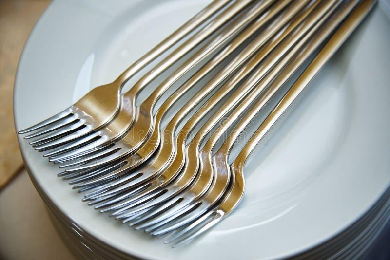 De vorken ligt op de stapel platen stock foto's