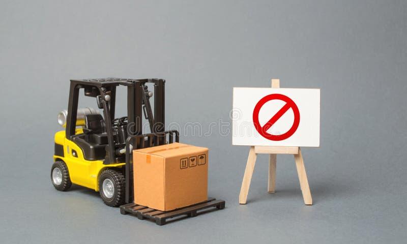 De vorkheftruck draagt een kartondoos dichtbij een tribune met een rood symbool nr Geen levering Beperking op de invoer van goede stock afbeelding