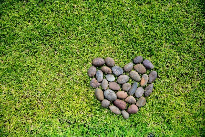 De vorm van het rotshart op een groen grassengebied stock foto