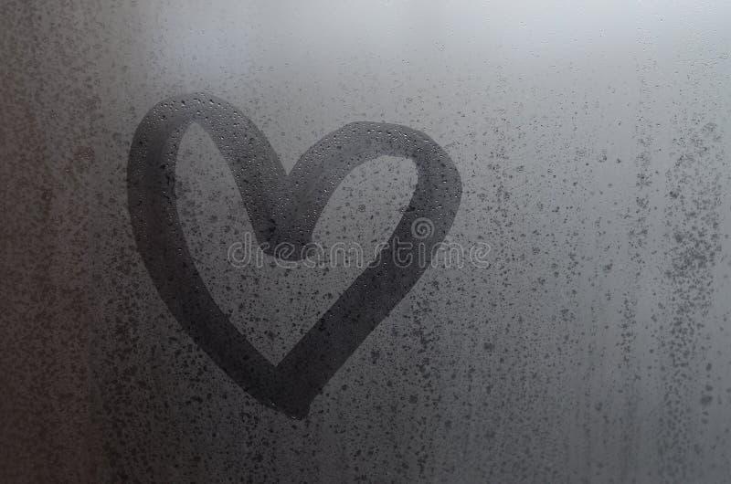 De vormhand van het liefdehart op natte, bevroren ruit met de achtergrond die van het ochtendzonlicht wordt getrokken Selectief n royalty-vrije stock fotografie