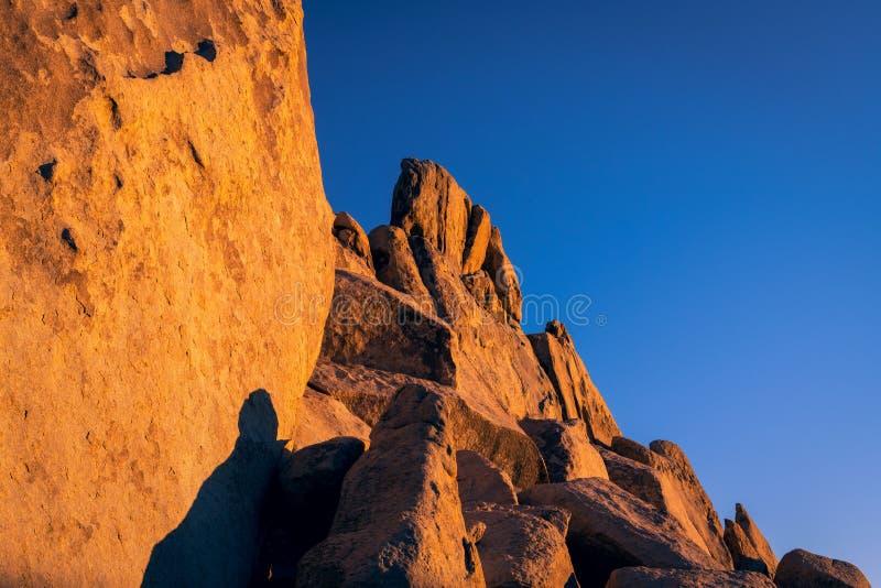 De vorming van de zandsteenrots, klip, en keien gloeiend sinaasappel en goud bij zonsondergang onder een diepe blauwe hemel in Jo stock afbeeldingen