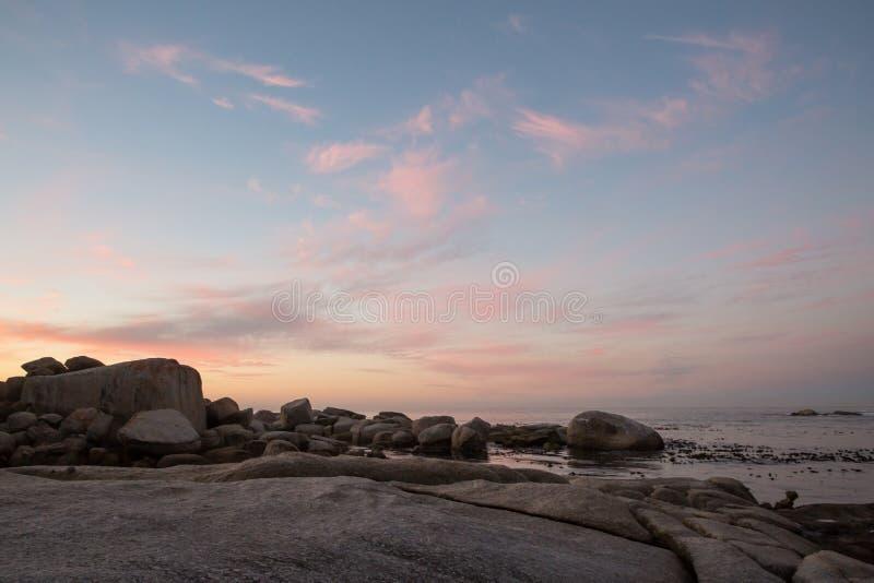 De vormingen van de kleurenwolk bij zonsondergang over het water stock afbeelding
