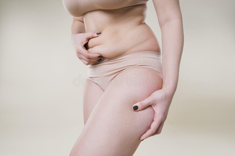 De vouwen van de vrouwenholding van huid, cellulite op vrouwelijk lichaam, beige achtergrond royalty-vrije stock afbeelding