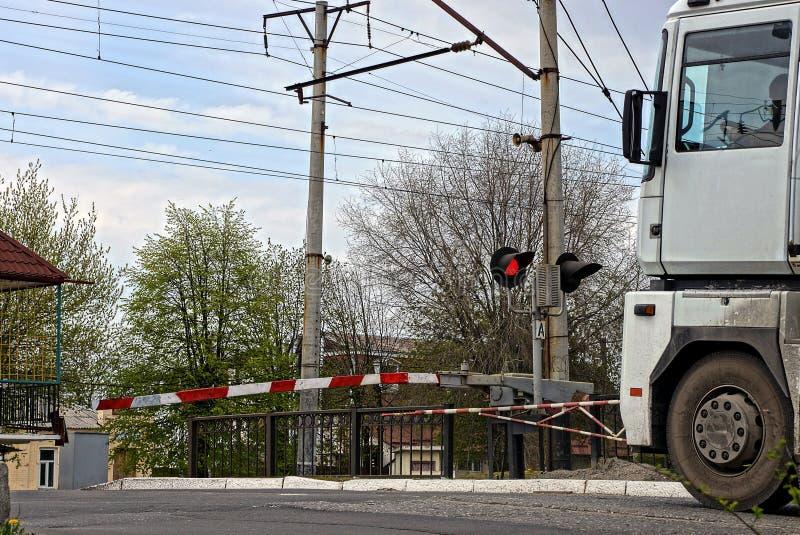 De vrachtwagen bevindt zich dichtbij de barrières bij de spoorwegovergang stock afbeelding