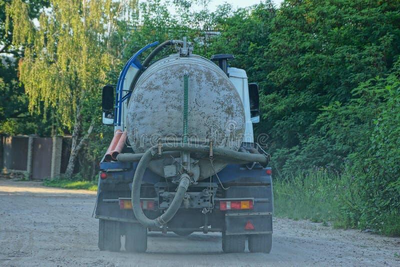 De vrachtwagen met een vat en een slang gaat op de weg royalty-vrije stock afbeelding