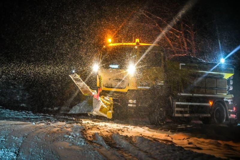 De vrachtwagen schoonmakende weg van het wegonderhoud tijdens zware sneeuwstorm in nacht, het gevaarlijke drijven tijdens de ramp stock afbeeldingen