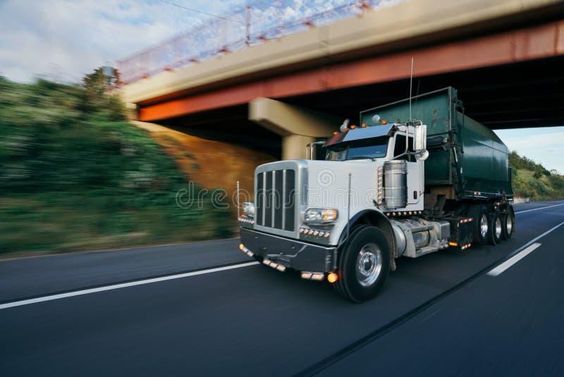 De vrachtwagen van het huisvuilafval op het onduidelijke beeldconcept van de wegmotie royalty-vrije stock afbeeldingen